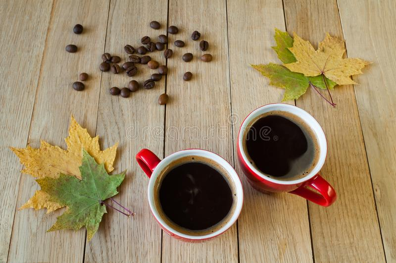 Two cups of coffee with autumn leaves and coffee beans on a wood stock photo