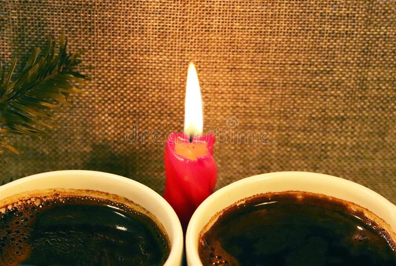 Two cups with coffee on the background of a red candle and a sprig of spruce. Romantic festive conversation at a hot heated drink. Meeting of man and woman royalty free stock photography