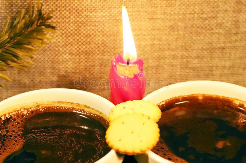 Two cups with coffee on the background of a red candle and a sprig of spruce. Romantic festive conversation at a hot heated drink. Meeting of man and woman stock photo