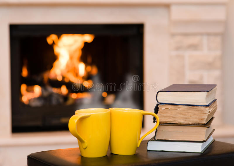 Two cups of coffee with books on the background of the fireplace stock photography