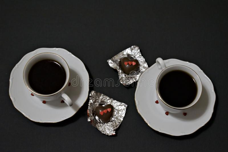 Two cups of coffee and two chocolate hearts on a dark tabletop. Valentine`s Day stock image