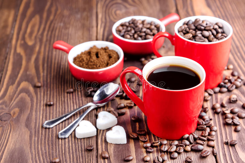 Two cups with coffee Cup with coffee beans Wooden background Coffee beans around red cups royalty free stock photos