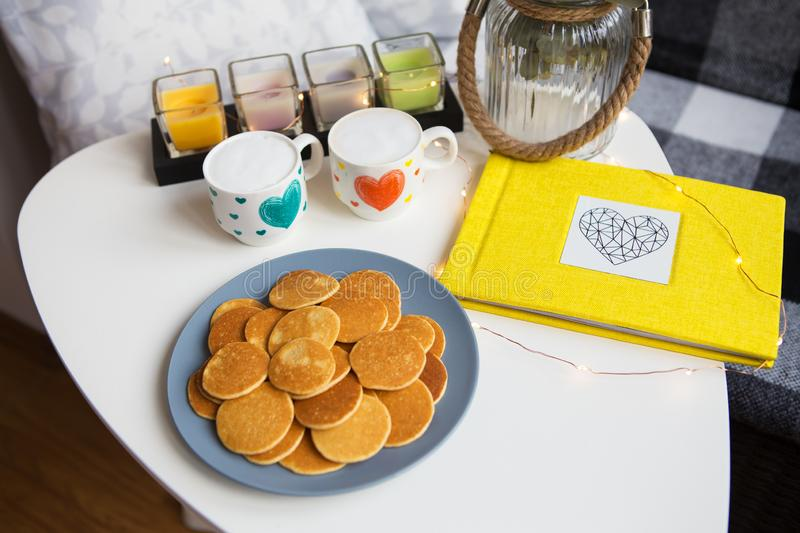 Two cups of coffee and delicious punkcakes stand on the table, yellow photo album, close-up stock photos