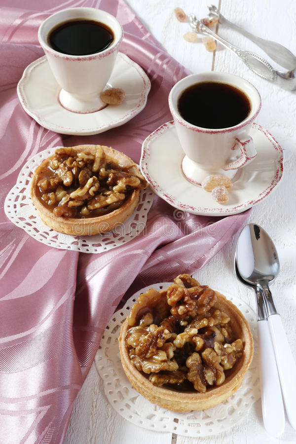 Two cups of coffee and a French dessert, Walnut caramel tart royalty free stock image