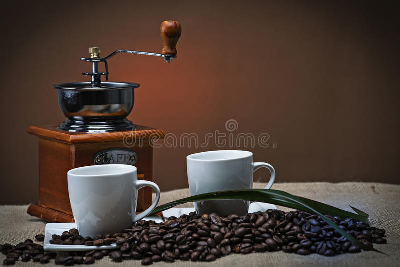 Two cups of coffee near to the grinde stock image