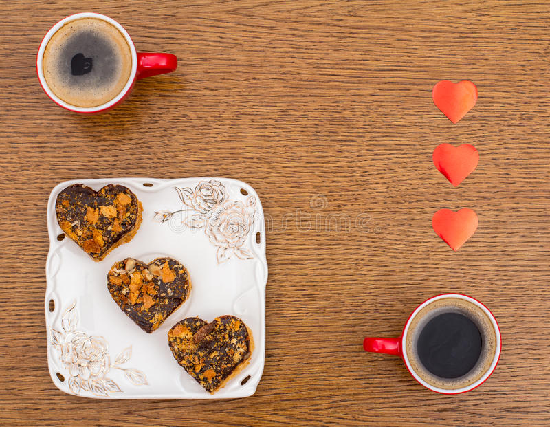 Two cups of coffee, a square plate with St Valentines Day cakes and hearts on a wo. Two red cups of coffee, white square dish with three heart-shaped cakes in stock photos