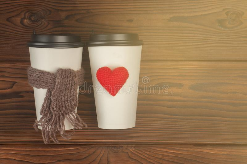 Two cups of coffee to go in white paper cups in sunlight. Morning coffee for couple in love. Knit heart and scarf. Place for text stock photos
