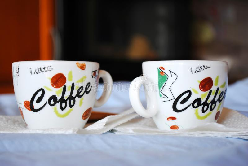 Two Cups of coffee on a white table. On a dark blurred background. Espresso royalty free stock photos