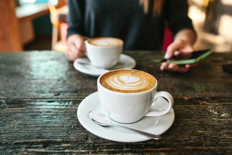 Two cups of coffee on a wooden table, a young girl holding a phone in her hand and going to call. Waiting for a meeting. Another person is late for the meeting stock photo