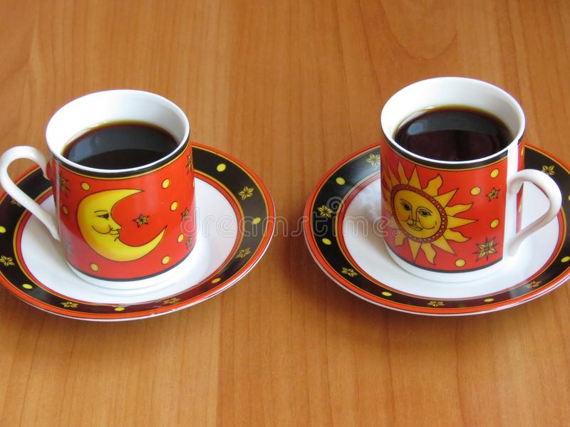 Two Cups of Dark Coffee in Red with Moon and Sun Elements. Two Cups of Dark Coffee in Red with Yellow Moon and Sun Elements on Wooden Table / Board. Copy Space stock photos