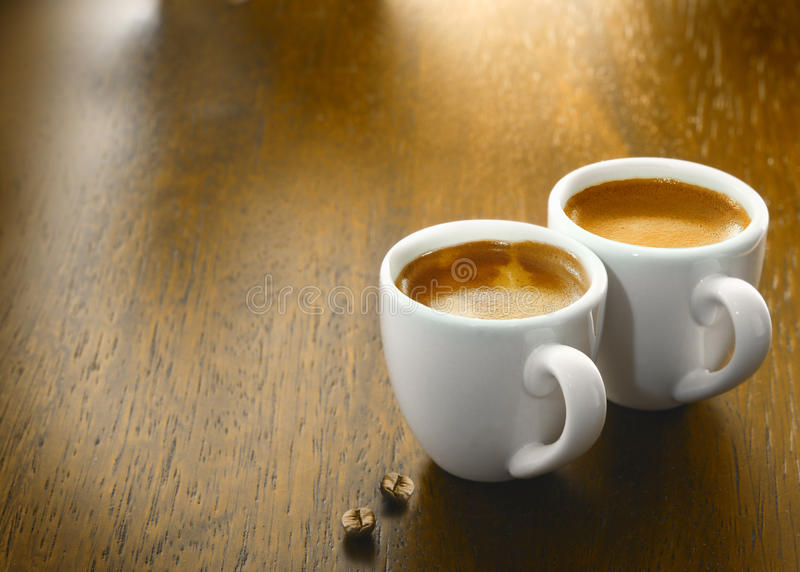 Two cups of freshly brewed espresso coffee. With two single coffee beans on a textured wooden table top with copyspace royalty free stock photography