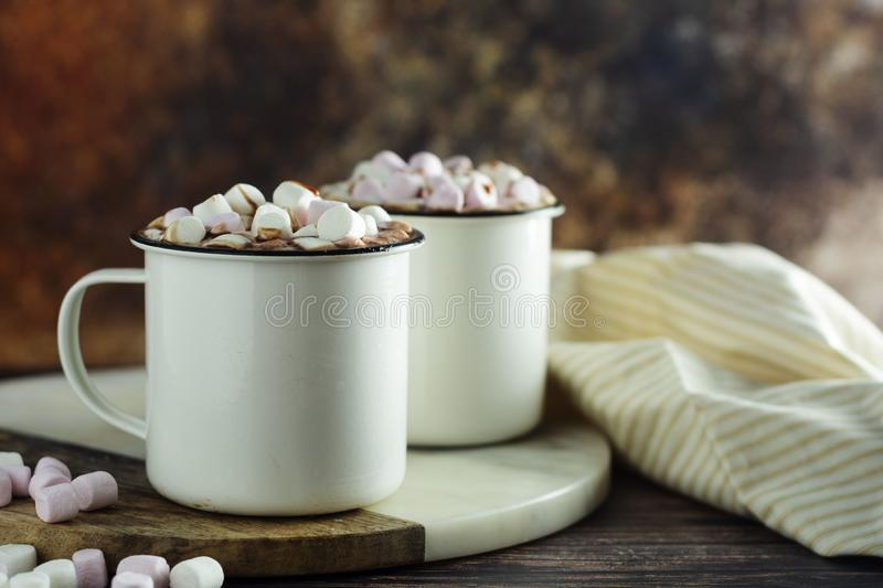 Two cups of hot chocolate, cocoa or warm drink with marshmallows on dark background stock image