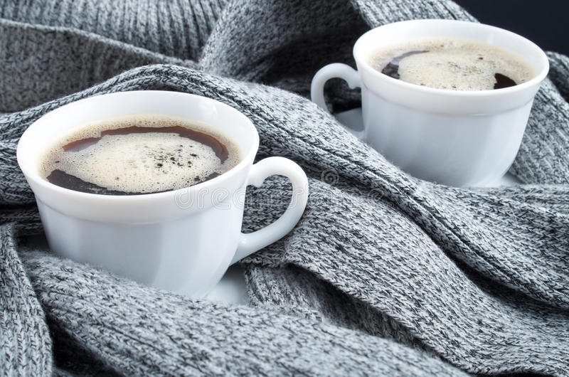 Two cups of hot coffee close up. Two cups of hot coffee in the folds of a gray scarf close-up with shallow depth of focus royalty free stock photography