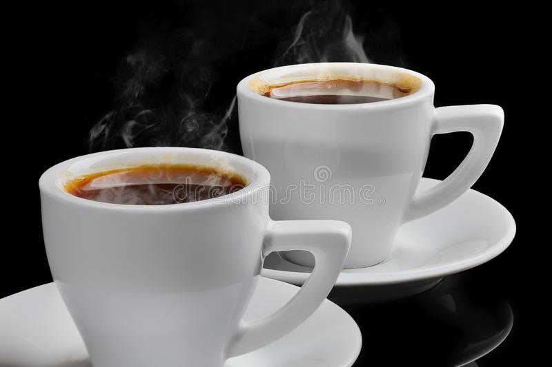 Two cups of hot coffee with steam on a black background. Two cups of hot coffee with steam on a black isolated background royalty free stock images