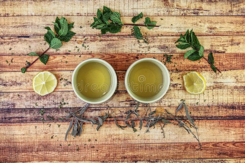 Two cups of hot drink for support own immunity. Curious herbals on wooden board. Nettle, lemon and mint leaves. Typical asian tea stock image