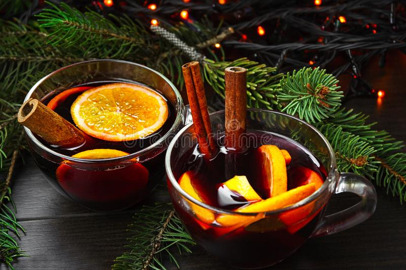 Two cups of mulled wine against the background of a garland and fir branches royalty free stock photos