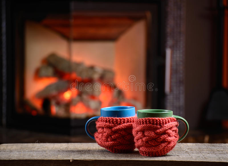 Two cups near the fireplace on vintage wooden table stock images