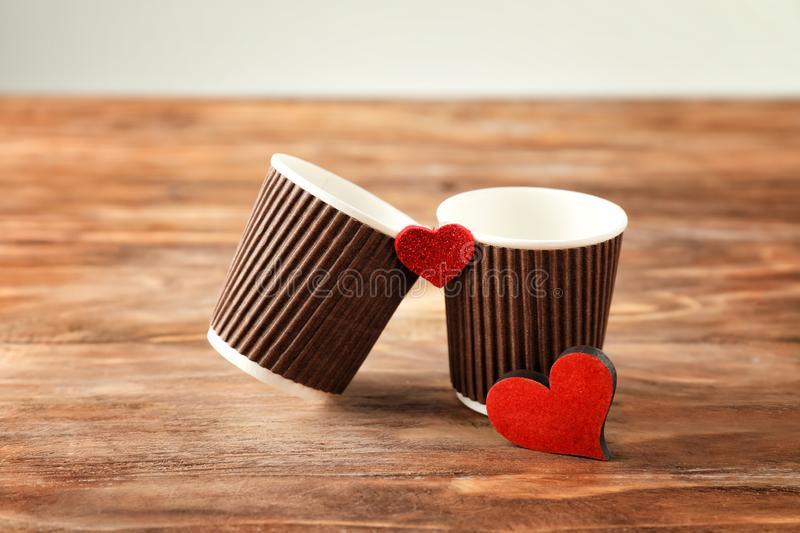 Two cups with red hearts on wooden table royalty free stock image