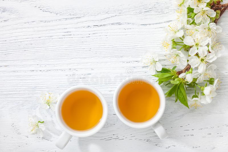 Two cups of tea and branch of blossom cherry on white wooden table stock images