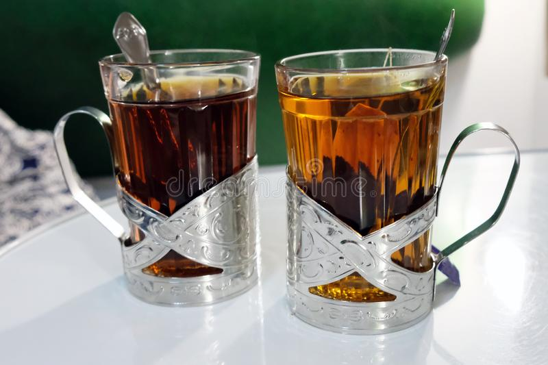 Two cups of tea in metal coasters stand on a white table. royalty free stock photography