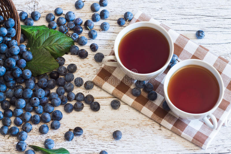 Two cups of tea on a napkin with a pattern in a cage on white wo. Two cups of tea on a napkin on white wooden background with blue berries blackthorn royalty free stock image