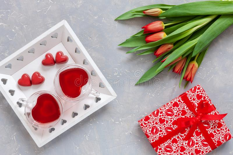 Two cups of tea, red chocolate candy, gift box with red ribbon and red tulips bouquet on light background. Concept for Women`s Da stock photos