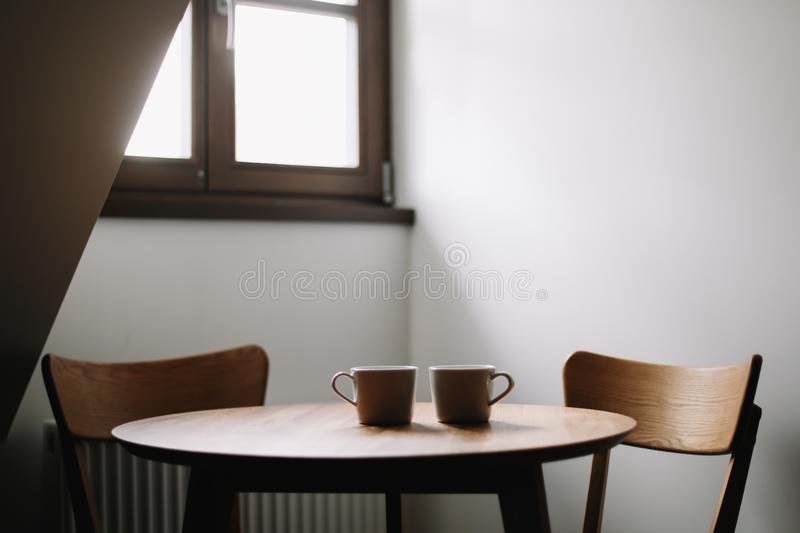 Two cups on wooden table. Dining room with table and two chairs. Modern minimal Scandinavian nordic interior. Morning coffee stock images