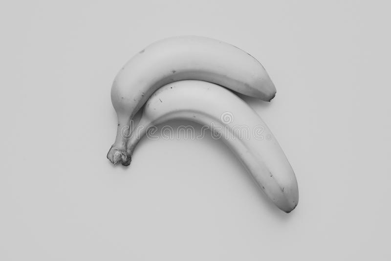 Pair of Light grey Banana. Two curved banana lying at light gey cardboard background giving the picture a nearly monochrome without color stock images