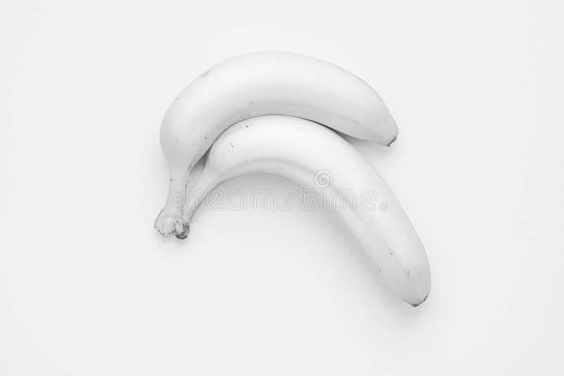 Pair of Light grey Banana. Two curved banana lying at light gey cardboard background giving the picture a nearly monochrome without color stock image