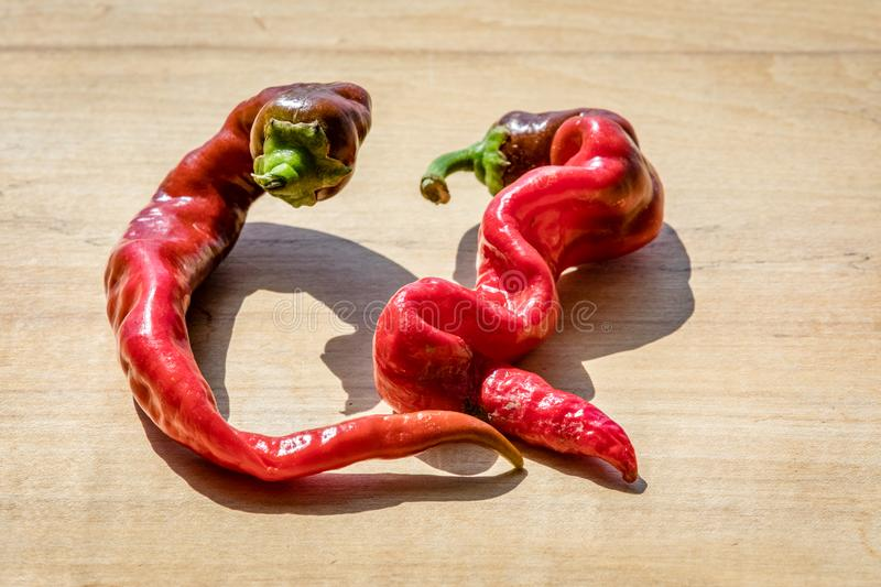 Curvy cayenne peppers on a wooden block next to each other stock photo