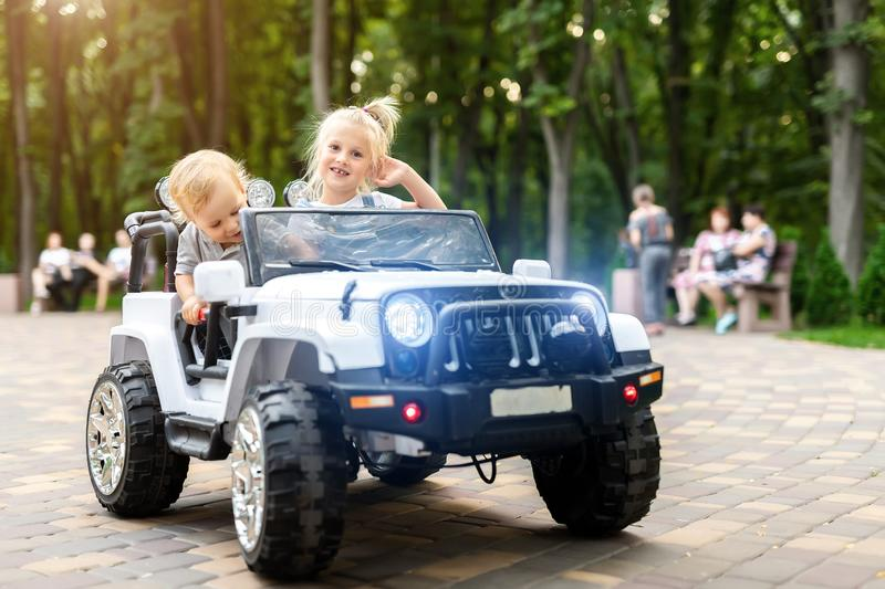 Two cute adorable blond sibings children having fun riding electric toy suv car in city park. Brother and sister enjoy playing and stock photo