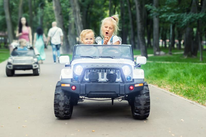 Two cute adorable blond sibings children having fun riding electric toy suv car in city park. Brother and sister enjoy playing and. Driving vehicle on city royalty free stock image