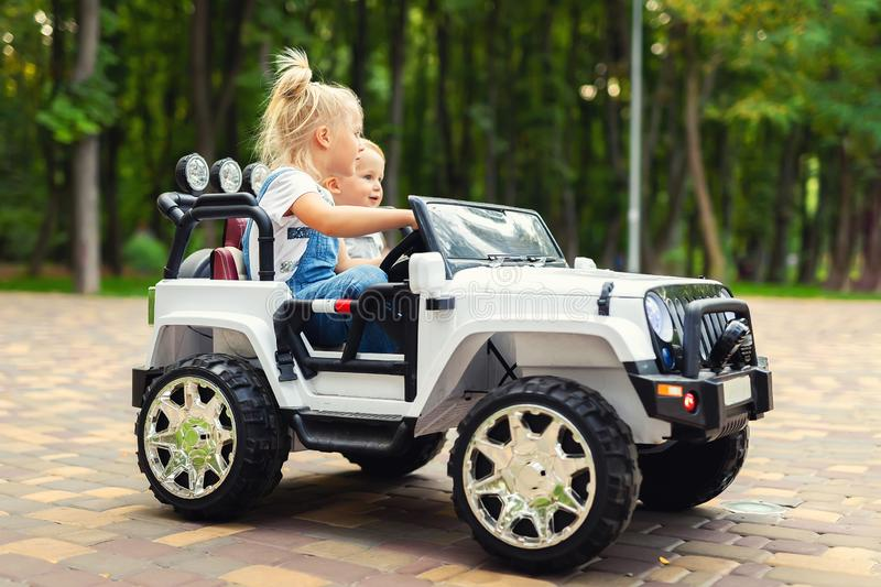 Two cute adorable blond sibings children having fun riding electric toy suv car in city park. Brother and sister enjoy playing and. Driving vehicle on city stock photos