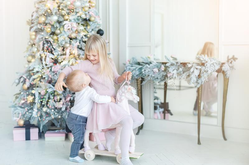 Two cute adorable little siblings brother and sister having fun playing with retro wooden wheel horse toy near christmas tree in. Cozy living room. Portrait of royalty free stock image