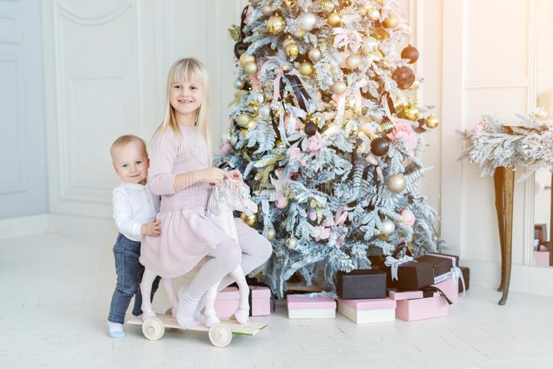 Two cute adorable little siblings brother and sister having fun playing with retro wooden wheel horse toy near christmas tree in. Cozy living room. Portrait of stock photo