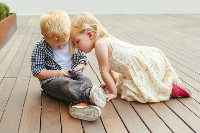 Two cute adorable white Caucasian toddlers boy and girl sitting together and playing games on cell mobile phone digital tablet. stock photography