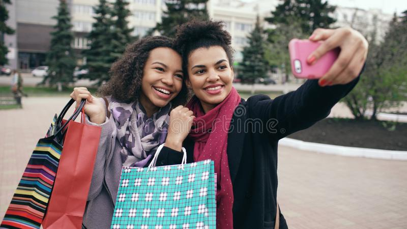 Two cute african american woman taking selfie with shopping bags and smiling. Friends have fun after visiting mall sale. royalty free stock image