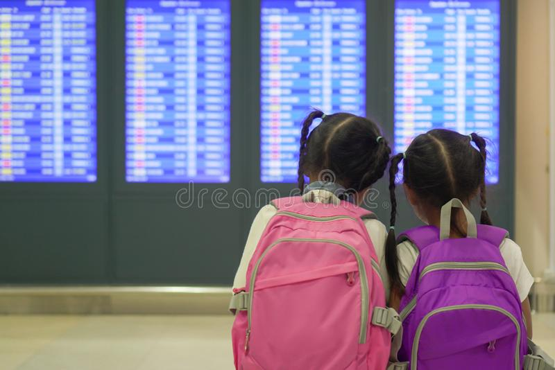 Two asian child girls with backpack checking their flight at information board in international airport terminal. Two cute asian child girls with backpack royalty free stock photography