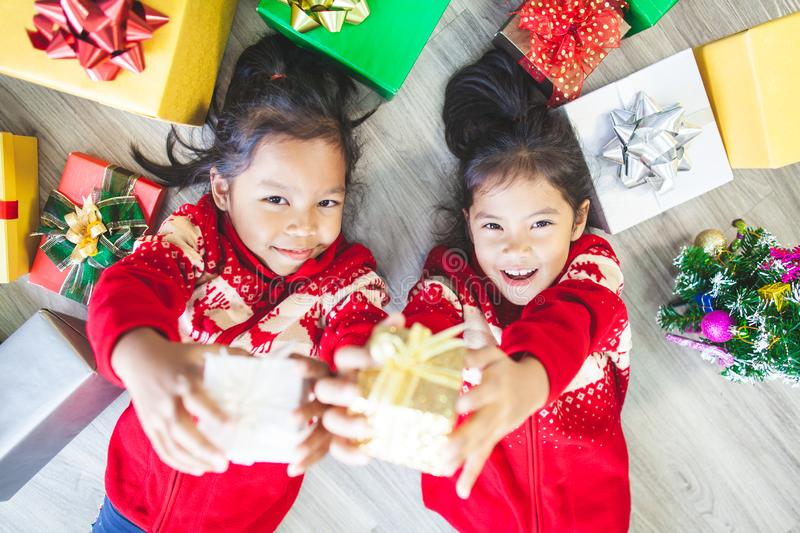 Two asian child girls laying down on the floor and giving gift boxes in Christmas celebration. Two cute asian child girls laying down on the floor and giving stock image
