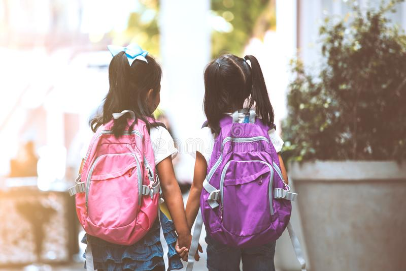 Two cute asian child girls with school bag holding hand and walk together in the school. Back to school. Two cute asian child girls with school bag holding hand stock photography