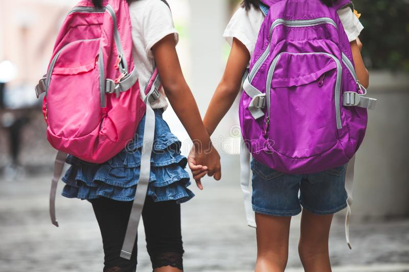 Two cute asian child girls with school bag holding hand and walk together in the school. Back to school. Two cute asian child girls with school bag holding hand royalty free stock photos