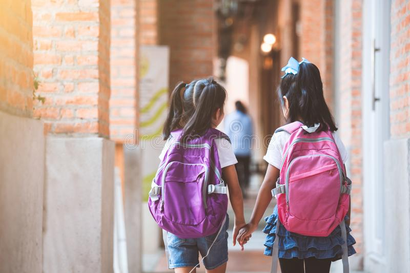 Two cute asian child girls with school bag holding hand and walk together in the school. Back to school. Two cute asian child girls with school bag holding hand stock images