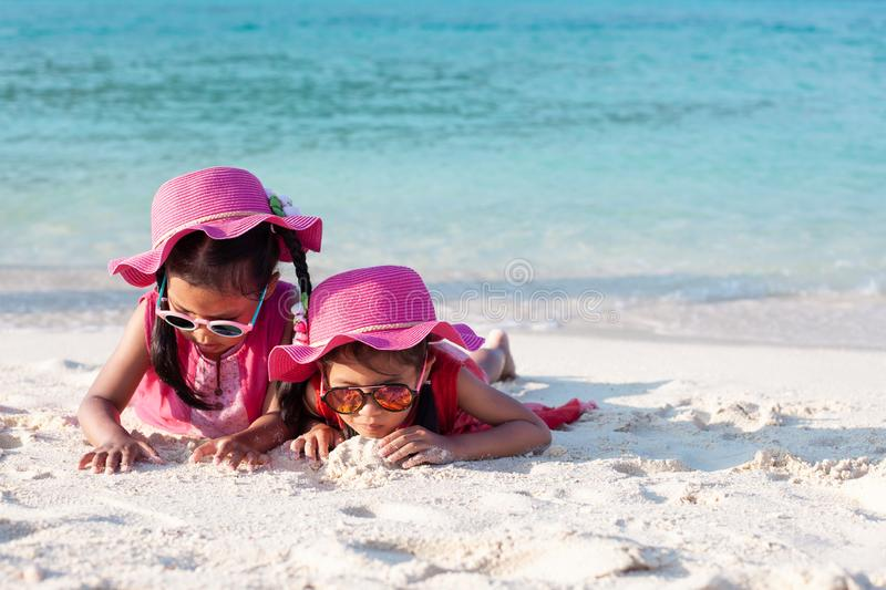 Two cute asian child girls wearing pink hat and sunglasses playing with sand together on the beach near the beautiful sea royalty free stock photography