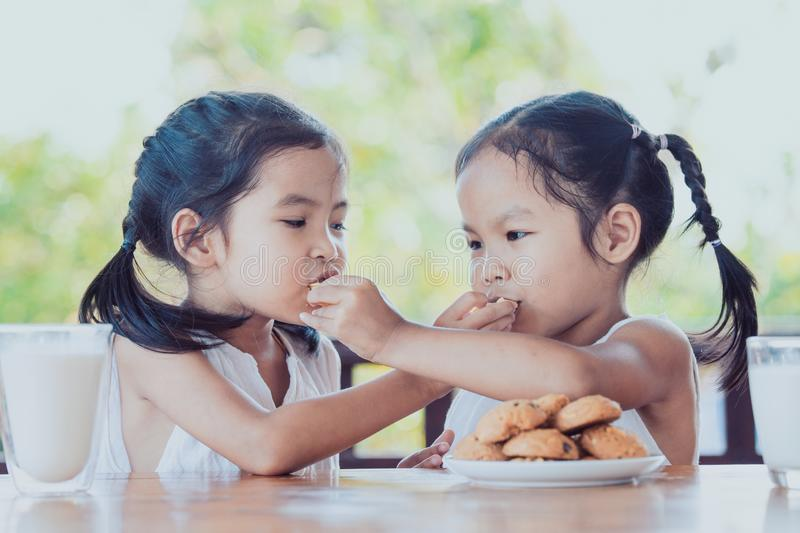 Two cute asian little child girls are eating cookies with milk. For breakfast together with happiness stock image