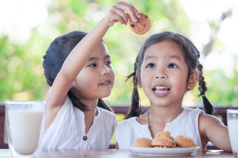 Two cute asian little child girls are eating cookies with milk. For breakfast together with happiness stock images