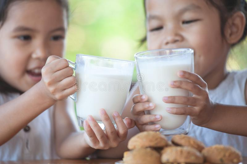 Two cute asian little child girls holding glass of milk royalty free stock image