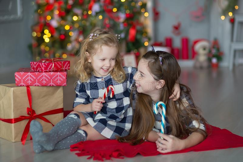 Two cute awesome girls sisters celebrating New Year Christmas close to xmas tree full of toys in stylish dresses with candies stock photography