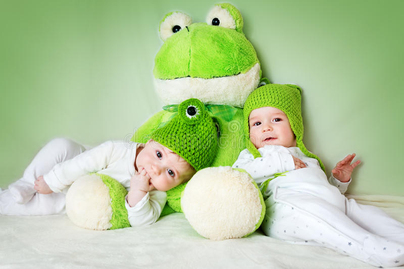 Two cute babies lying in frog hats with a soft toy royalty free stock photography
