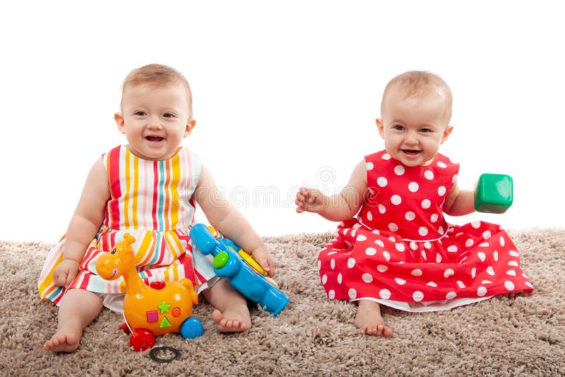 Two cute baby girls playing with toys at home, isolated on white stock images
