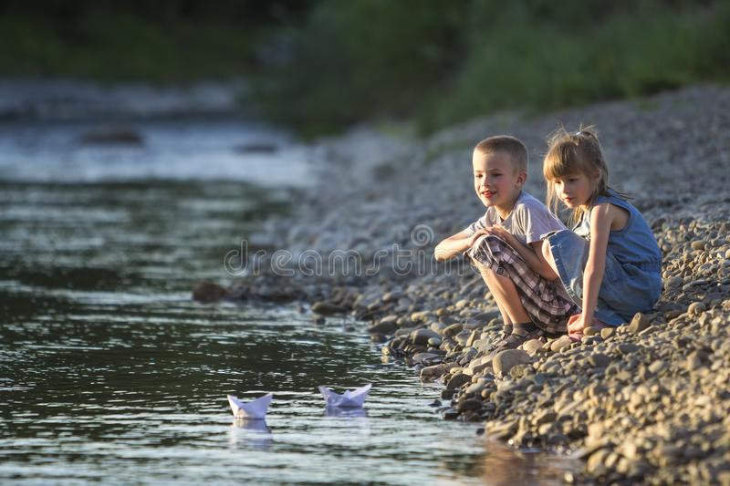 Two cute blond children, boy and girl on river bank sending in w royalty free stock photo